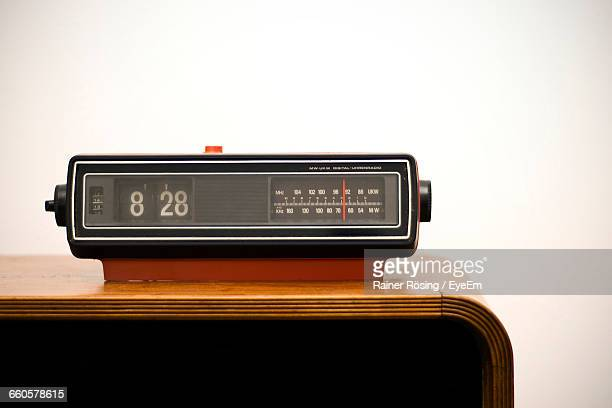 Close-Up Of Old-Fashioned Radio With Alarm Clock On Sideboard