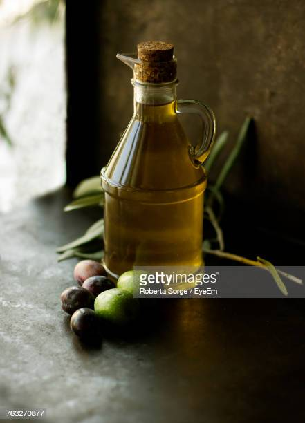 close-up of olive oil bottle on table - olive oil stock pictures, royalty-free photos & images