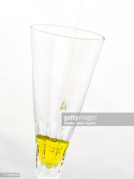 Close-Up Of Olive Oil In Glass Against White Background