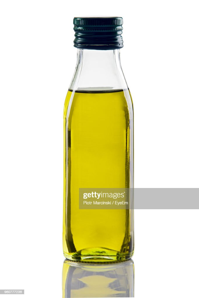 Closeup Of Olive Oil In Glass Bottle Against White