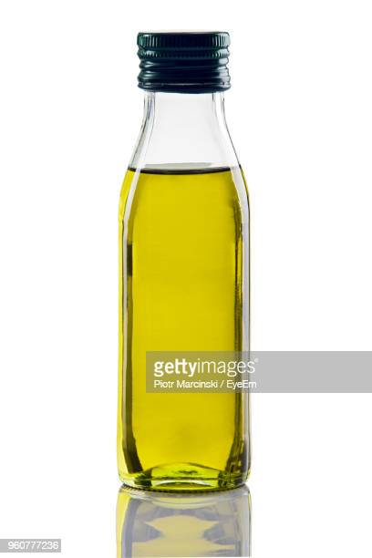 close-up of olive oil in glass bottle against white background - olive oil stock pictures, royalty-free photos & images