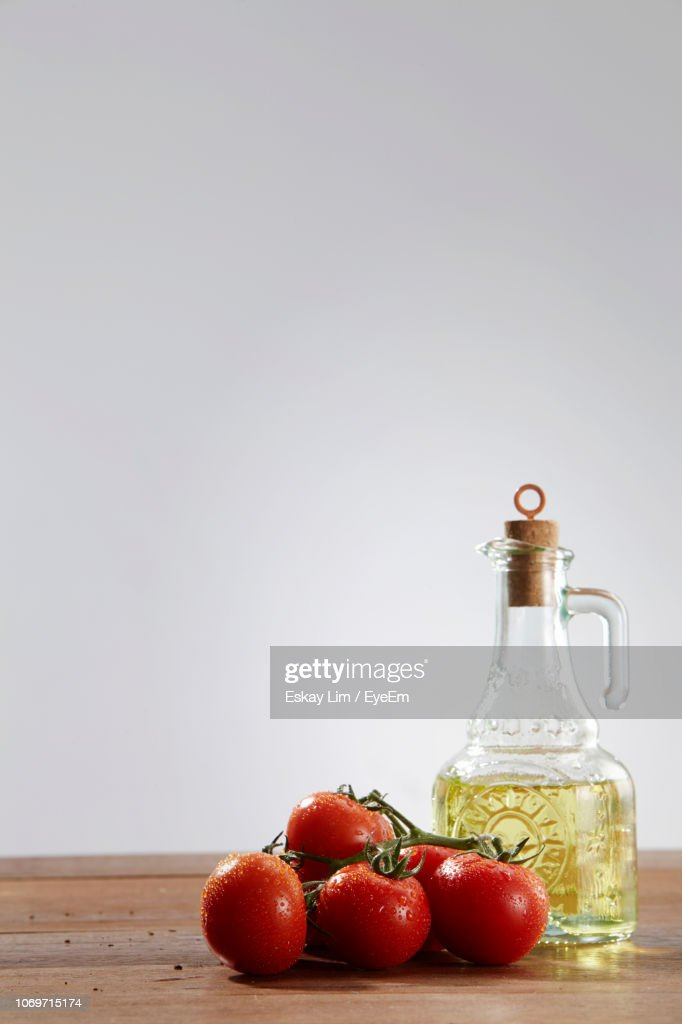Closeup Of Olive Oil In Jar With Fresh Tomatoes On Table