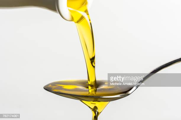 close-up of olive oil pouring on spoon from container against white background - olive oil stock pictures, royalty-free photos & images