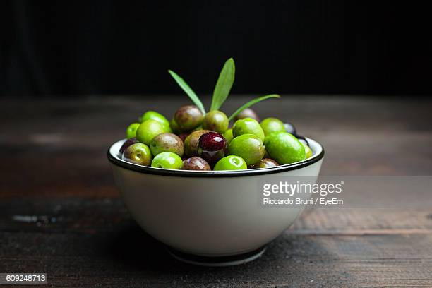 close-up of olives in bowl on table - aceitunas fotografías e imágenes de stock
