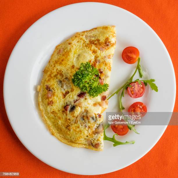 Close-Up Of Omelet With Cherry Tomato Served In Plate On Table