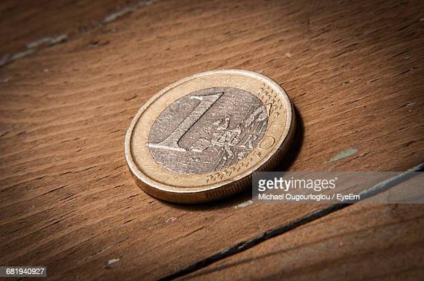 Close-Up Of One Euro Coin On Wooden Table