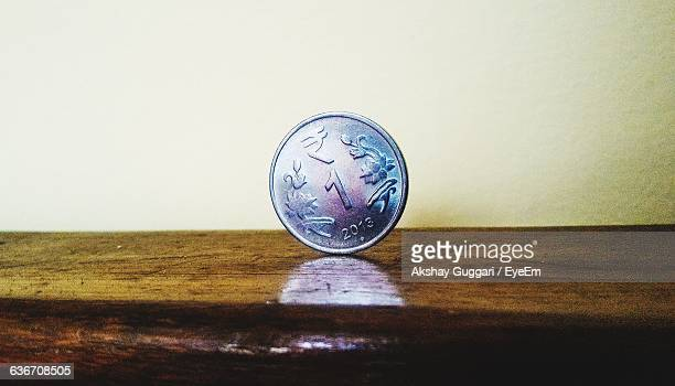 Close-Up Of One Rupee Coin On Wooden Table
