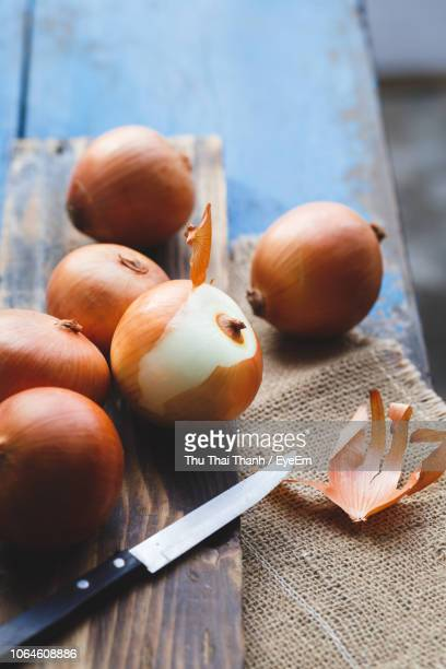 close-up of onions and knife on table - 果物の皮 ストックフォトと画像