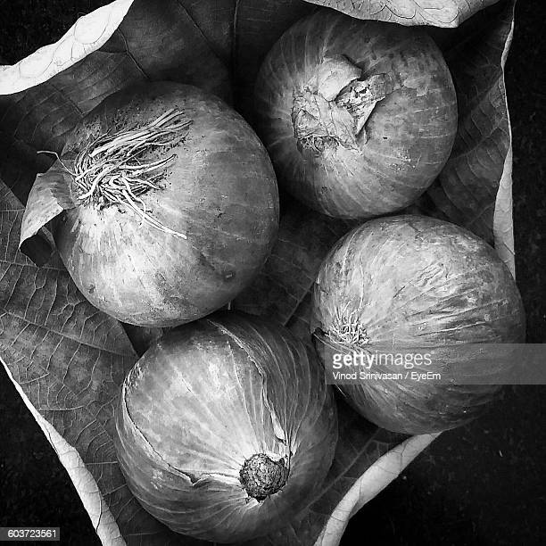 close-up of onions on dry leaf at table - black and white vegetables stock photos and pictures