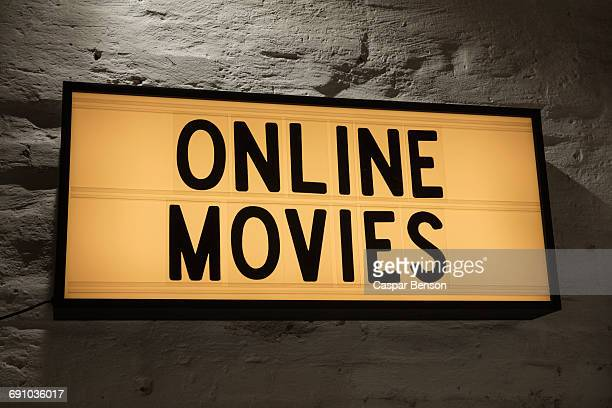 Close-up of Online Movies signboard against gray wall