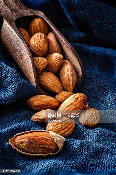 close-up of open almonds in a group coming out from a serving scoop - almond stock pictures, royalty-free photos & images