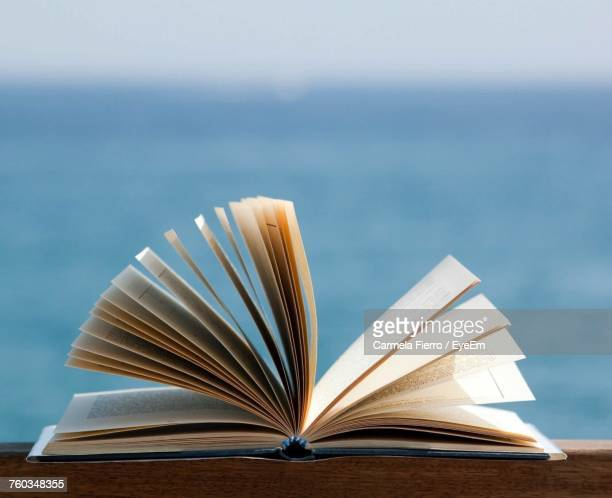 Close-Up Of Open Book Against Sea