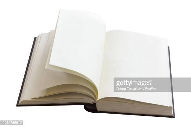 close-up of open book against white background - open book stock photos and pictures