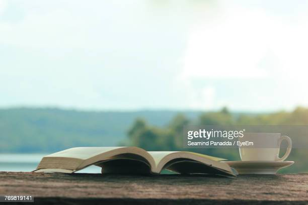 Close-Up Of Open Book And Coffee Against Sky
