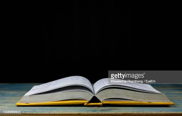 close-up of open book on table against black background - open book stock photos and pictures