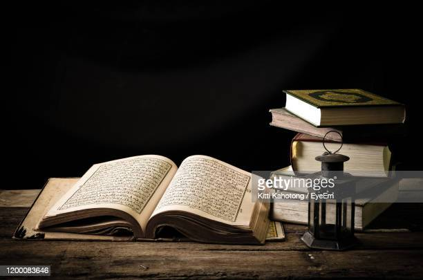 close-up of open book on table against black background - koran stock pictures, royalty-free photos & images