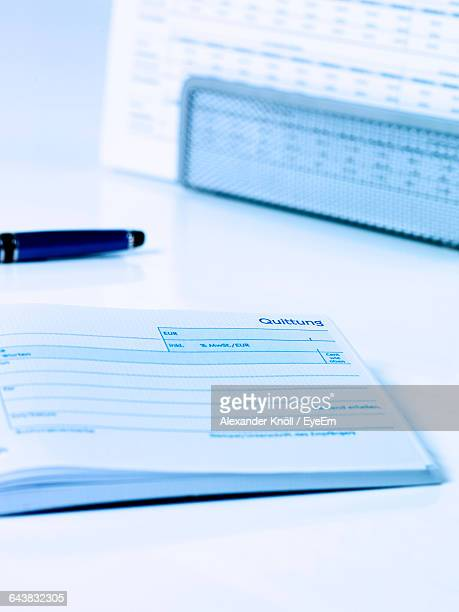 close-up of open receipt pad and pen on table - レシピ帳 ストックフォトと画像