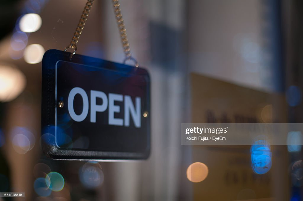 Close-Up Of Open Sign Hanging From Glass Window Of Store : Stock Photo