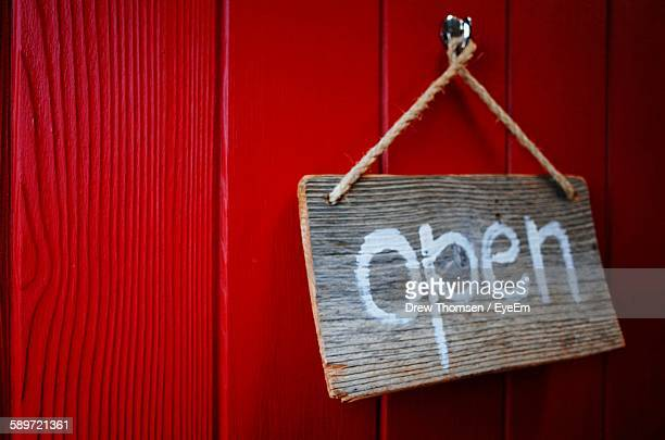 Close-Up Of Open Sign On Wooden Plank Hanging To Wall