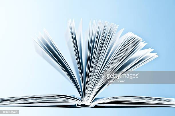 Close-up of opened hardcover book with pages on blue background
