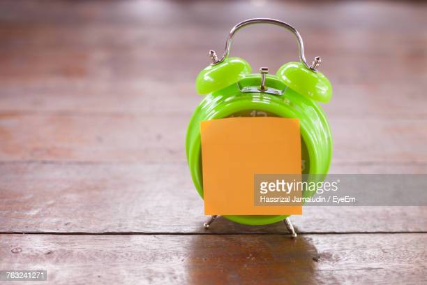 Close-Up Of Orange Adhesive Note On Alarm Clock At Wooden Table