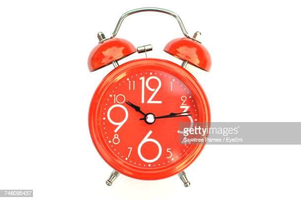 Close-Up Of Orange Alarm Clock Against White Background