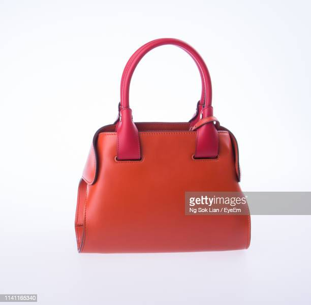 close-up of orange bag against white background - borsetta da sera foto e immagini stock