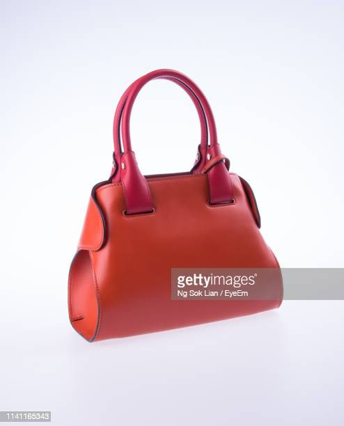 close-up of orange bag against white background - brown purse stock pictures, royalty-free photos & images