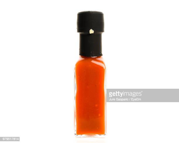 close-up of orange bottle against white background - condiment stock pictures, royalty-free photos & images
