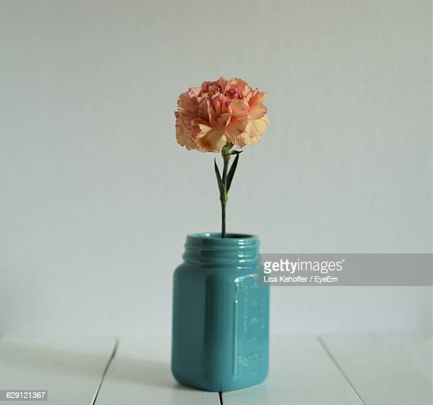 Close-Up Of Orange Carnation In Jar On Table At Home