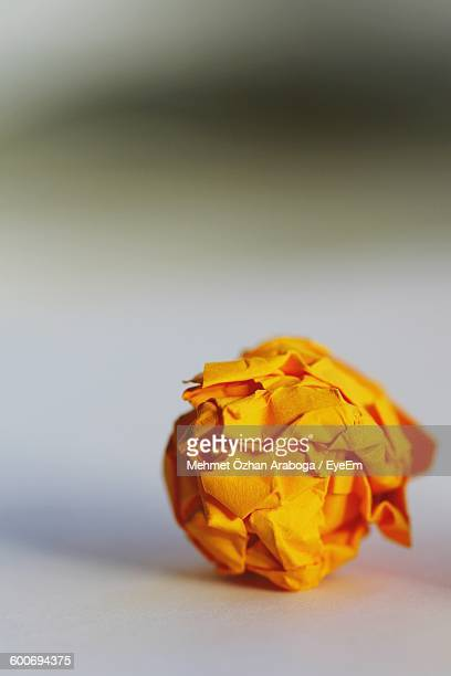 Close-Up Of Orange Crumpled Paper On Table