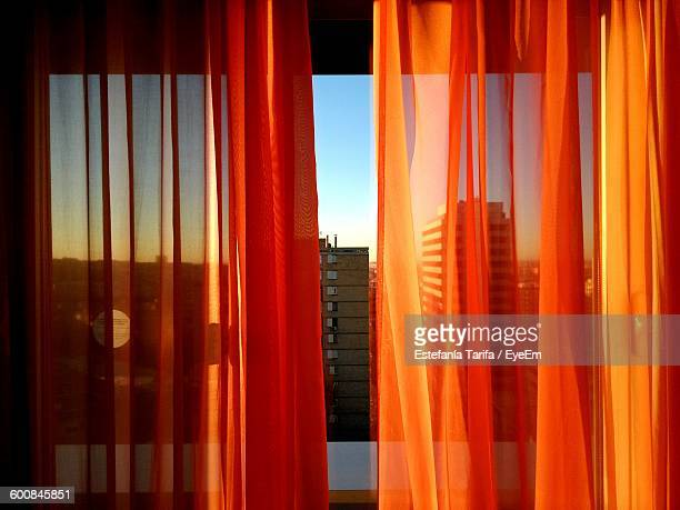 Close-Up Of Orange Curtains At Window Against Buildings In City