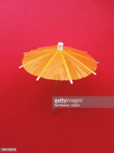Close Up Of Orange Drink Umbrella Against Red Background