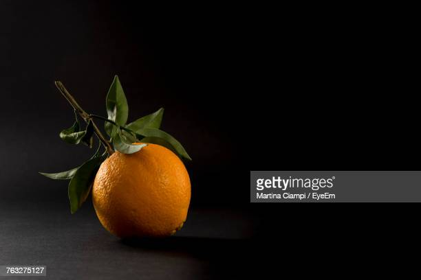 close-up of orange fruit against black background - orange stock pictures, royalty-free photos & images