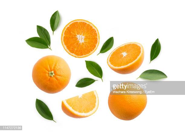 close-up of orange fruits and leaves against white background - oranje stockfoto's en -beelden