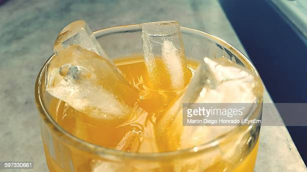 Close-Up Of Orange Juice With Ice Served In Glass On Table