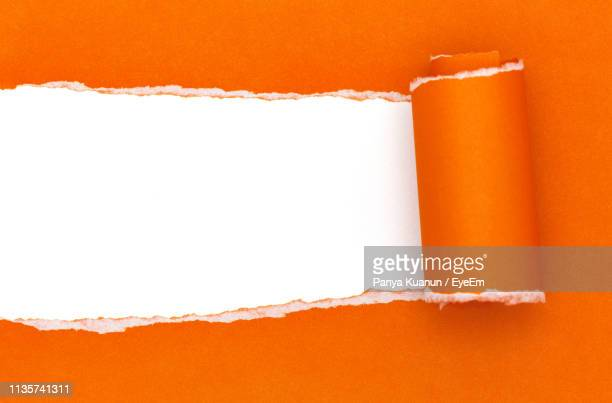 close-up of orange paper against white background - torn stock pictures, royalty-free photos & images