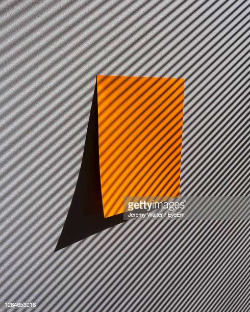 close-up of orange paper on shadow-striped wall - eyeem jeremy walter stock pictures, royalty-free photos & images
