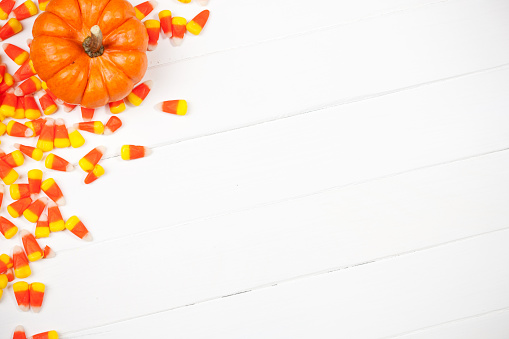 Close-Up Of Orange Pumpkin And Candies Against White Background - gettyimageskorea