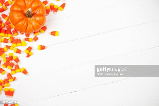 Close-Up Of Orange Pumpkin And Candies Against White Background