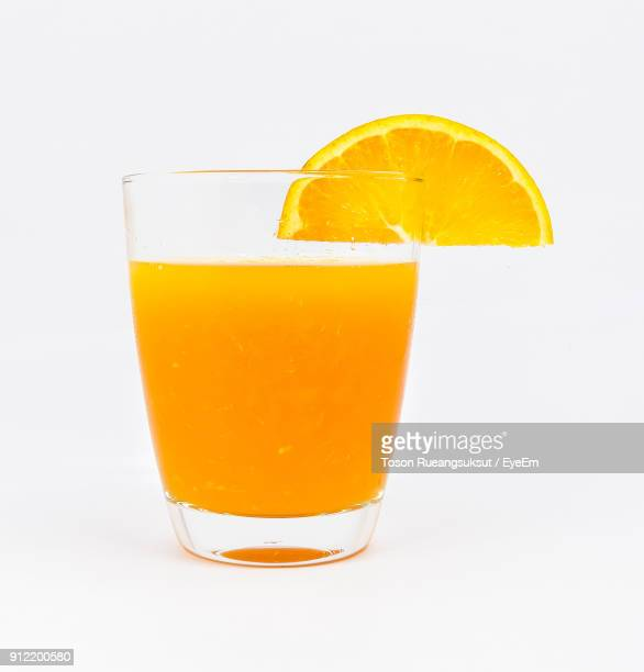 Close-Up Of Orange Slice On Drink Against White Background