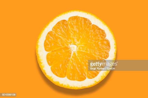 close-up of orange slice over orange background - naranja fotografías e imágenes de stock