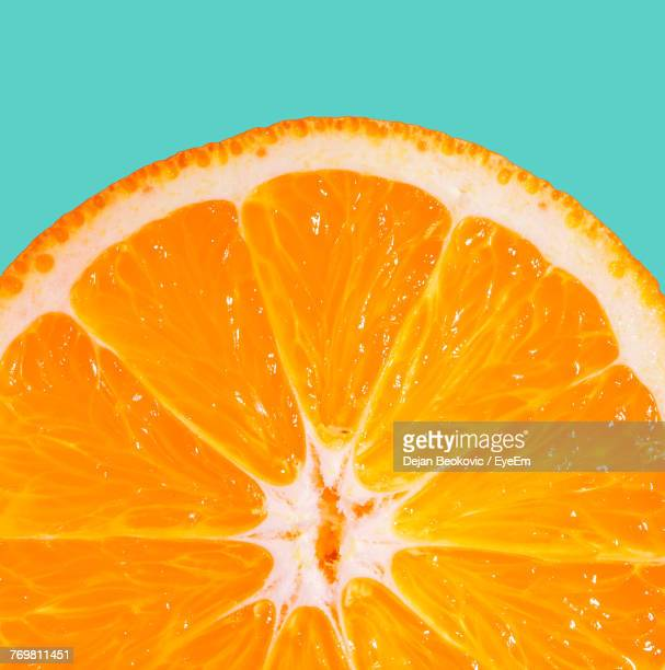 Close-Up Of Orange Slices Against Green Background