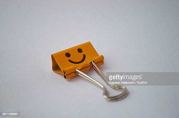 Close-Up Of Orange Smiley Paper Clip Against White Background