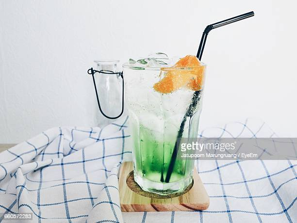 Close-Up Of Orange Soda On Table Against White Wall