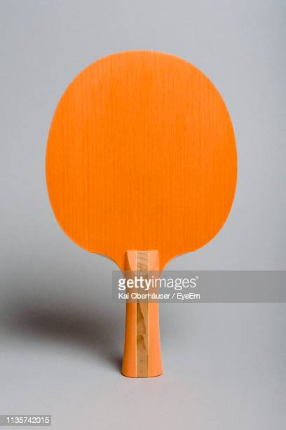 close-up of orange table tennis bat against gray background - racquet stock pictures, royalty-free photos & images