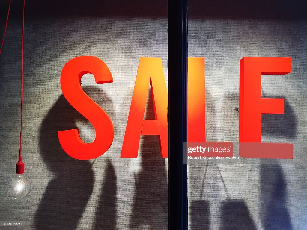 Close-Up Of Orange Text In Store Window With Hanging Light Bulb : Stock Photo