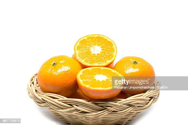 Close-Up Of Oranges In Basket Over White Background