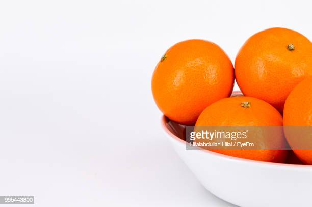 close-up of oranges in bowl on white background - hilal stock photos and pictures