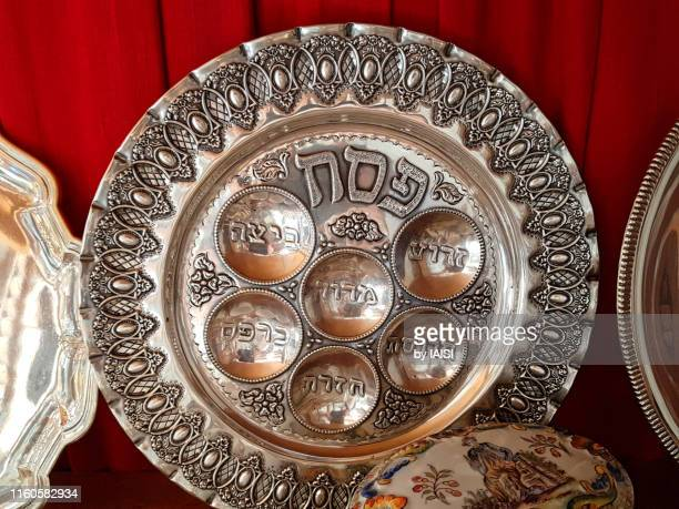 close-up of ornate passover seder plate engraved with the names of the symbolic foods placed on it on the passover evening - passover symbols stock pictures, royalty-free photos & images